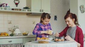 Χαριτωμένο κορίτσι που βοηθά τη μητέρα της στη ζύμη ανακατώματος κουζινών για τα μπισκότα στο κύπελλο Το Mom έχει τη λερώνοντας μ απόθεμα βίντεο