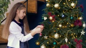 Χαριτωμένο κορίτσι που διακοσμεί το χριστουγεννιάτικο δέντρο με το ζωηρόχρωμο μπιχλιμπίδι φιλμ μικρού μήκους