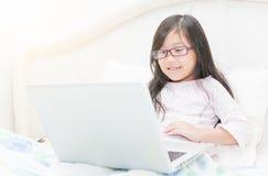 Χαριτωμένο κορίτσι που εργάζεται στην έννοια φορητών προσωπικών υπολογιστών για την εκπαίδευση Στοκ Φωτογραφίες