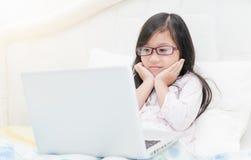 Χαριτωμένο κορίτσι που εργάζεται στην έννοια φορητών προσωπικών υπολογιστών για την εκπαίδευση Στοκ Εικόνες
