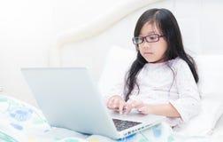 Χαριτωμένο κορίτσι που εργάζεται στο φορητό προσωπικό υπολογιστή Στοκ Φωτογραφία