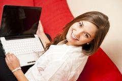 Χαριτωμένο κορίτσι που εργάζεται στο lap-top της στο σπίτι Στοκ Εικόνες
