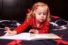 Χαριτωμένο κορίτσι που διαβάζει ένα βιβλίο στο κρεβάτι Στοκ φωτογραφίες με δικαίωμα ελεύθερης χρήσης