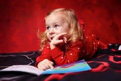 Χαριτωμένο κορίτσι που διαβάζει ένα βιβλίο στο κρεβάτι Στοκ Εικόνες