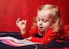 Χαριτωμένο κορίτσι που διαβάζει ένα βιβλίο στο κρεβάτι Στοκ Φωτογραφία