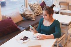 Χαριτωμένο κορίτσι που διαβάζει τις ειδήσεις πρωινού στην έξυπνη τηλεφωνική συνεδρίαση στον καφέ Στοκ Εικόνες