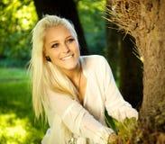 Χαριτωμένο κορίτσι που κοιτάζει έξω από πίσω από ένα δέντρο Στοκ Φωτογραφία