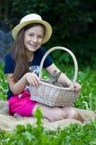Χαριτωμένο κορίτσι που κρατά ένα καλάθι με το κουνέλι Στοκ Φωτογραφία