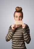 Χαριτωμένο κορίτσι που κρατά την άσπρη κάρτα στο μέτωπο των χειλιών της με το αντίγραφο spac στοκ φωτογραφία με δικαίωμα ελεύθερης χρήσης