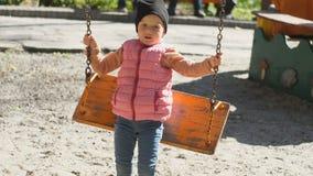 Χαριτωμένο χαριτωμένο κορίτσι που οδηγά σε μια ταλάντευση μια όμορφη ηλιόλουστη ημέρα φθινοπώρου Οικογενειακή ημέρα απόθεμα βίντεο