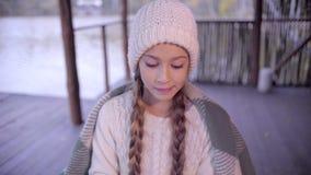 Χαριτωμένο κορίτσι που πίνει το καυτό τσάι στη λίμνη που τυλίγεται στο καρό απόθεμα βίντεο