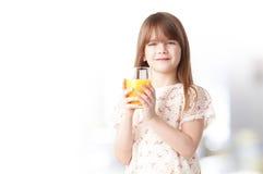 Χαριτωμένο κορίτσι που πίνει το χυμό από πορτοκάλι Στοκ Φωτογραφία