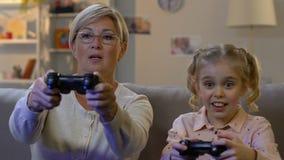 Χαριτωμένο κορίτσι που παίζει το τηλεοπτικό παιχνίδι μαζί με τη γιαγιά, που παρουσιάζει ψυχαγωγία νεολαίας απόθεμα βίντεο