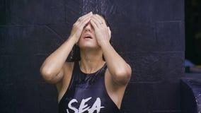 Χαριτωμένο κορίτσι που στέκεται κάτω από το ντους υπαίθρια Κορίτσι στις στάσεις μαγιό στο σκούρο γκρι τοίχο Θερμαίνεται κάτω από  φιλμ μικρού μήκους