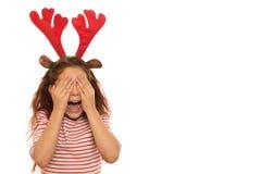 Χαριτωμένο κορίτσι που φορά τα ελαφόκερες Χριστουγέννων στοκ εικόνες