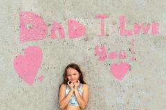 Χαριτωμένο κορίτσι που χαμογελά στο υπόβαθρο του τοίχου με τον μπαμπά λέξεων σ' αγαπώ Έννοια της ευτυχούς ημέρας πατέρων στοκ εικόνα