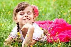 Χαριτωμένο κορίτσι που χαμογελά στη χλόη Στοκ εικόνα με δικαίωμα ελεύθερης χρήσης