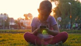 Χαριτωμένο κορίτσι που χρησιμοποιεί τη συνεδρίαση smartphone στο χορτοτάπητα στο κεντρικό πάρκο Το νέο χαριτωμένο κορίτσι κάνει τ φιλμ μικρού μήκους