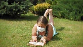 Χαριτωμένο κορίτσι σε μια αναπνευστική συσκευή που διαβάζει ένα βιβλίο στο πάρκο απόθεμα βίντεο