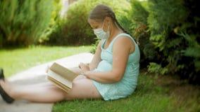 Χαριτωμένο κορίτσι σε μια αναπνευστική συσκευή που διαβάζει ένα βιβλίο στο πάρκο σε έναν πάγκο απόθεμα βίντεο