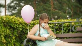 Χαριτωμένο κορίτσι σε μια αναπνευστική συσκευή που διαβάζει ένα βιβλίο στο πάρκο σε έναν πάγκο φιλμ μικρού μήκους
