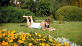 Χαριτωμένο κορίτσι σε μια αναπνευστική συσκευή που διαβάζει ένα βιβλίο στο πάρκο φιλμ μικρού μήκους
