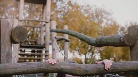 Χαριτωμένο κορίτσι στη σειρά μαθημάτων σχοινιών πάρκων περιπέτειας Ευτυχή τρεξίματα παιδιών στη γέφυρα σχοινιών μετ' εμποδίων pla απόθεμα βίντεο
