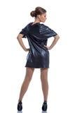 Χαριτωμένο κορίτσι στη σκούρο μπλε τοποθέτηση φορεμάτων πίσω στη κάμερα στοκ φωτογραφία με δικαίωμα ελεύθερης χρήσης