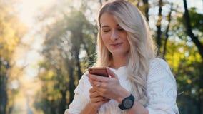 Χαριτωμένο κορίτσι στο άσπρο μήνυμα γραψίματος πουλόβερ στο smartphone της υπαίθρια Γυναίκα που χρησιμοποιεί την ψηφιακή συσκευή, φιλμ μικρού μήκους
