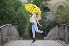 Χαριτωμένο κορίτσι στο κίτρινο πουκάμισο και τζιν που περπατούν στη γέφυρα με μια φωτεινή ομπρέλα στο βράδυ στοκ φωτογραφία