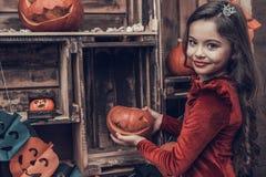 Χαριτωμένο κορίτσι στο κοστούμι αποκριών με τη χαρασμένη κολοκύθα στοκ φωτογραφία με δικαίωμα ελεύθερης χρήσης