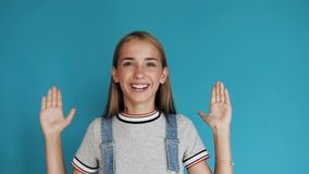 Χαριτωμένο κορίτσι σχετικά με το πρόσωπο με τα χέρια, που χαμογελούν και που κοιτάζουν επίμονα στη κάμερα στεμένος στο μπλε κλίμα φιλμ μικρού μήκους