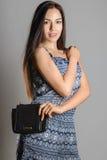 Χαριτωμένο κορίτσι brunette με τη μακριά ρέοντας τρίχα που κρατά τη μαύρη τσάντα στοκ εικόνα