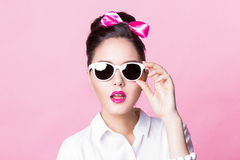 Χαριτωμένο κορίτσι brunette στα μοντέρνα γυαλιά με το ακριβές τόξο hairstyle Στοκ Φωτογραφία