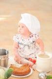 Χαριτωμένο κορίτσι liitle στη συνεδρίαση καπέλων αρχιμαγείρων ` s στο χώμα πατωμάτων κουζινών Στοκ εικόνες με δικαίωμα ελεύθερης χρήσης