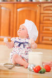 Χαριτωμένο κορίτσι liitle στη συνεδρίαση καπέλων αρχιμαγείρων ` s στο χώμα πατωμάτων κουζινών Στοκ φωτογραφίες με δικαίωμα ελεύθερης χρήσης
