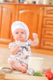 Χαριτωμένο κορίτσι liitle στη συνεδρίαση καπέλων αρχιμαγείρων ` s στο χώμα πατωμάτων κουζινών Στοκ εικόνα με δικαίωμα ελεύθερης χρήσης