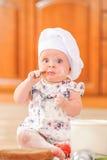 Χαριτωμένο κορίτσι liitle στη συνεδρίαση καπέλων αρχιμαγείρων ` s στο χώμα πατωμάτων κουζινών Στοκ Εικόνες