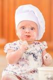 Χαριτωμένο κορίτσι liitle στη συνεδρίαση καπέλων αρχιμαγείρων ` s στο χώμα πατωμάτων κουζινών Στοκ φωτογραφία με δικαίωμα ελεύθερης χρήσης