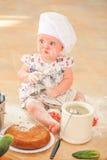 Χαριτωμένο κορίτσι liitle στη συνεδρίαση καπέλων αρχιμαγείρων ` s στο χώμα πατωμάτων κουζινών Στοκ Εικόνα