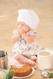 Χαριτωμένο κορίτσι liitle στη συνεδρίαση καπέλων αρχιμαγείρων ` s στο χώμα πατωμάτων κουζινών Στοκ Φωτογραφίες