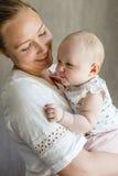 Χαριτωμένο κοριτσάκι με τη χαμογελώντας και φροντίζοντας μητέρα της Στοκ φωτογραφία με δικαίωμα ελεύθερης χρήσης