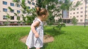 Χαριτωμένο κοριτσάκι που περπατά στη χλόη στο πάρκο πόλεων, σε αργή κίνηση απόθεμα βίντεο