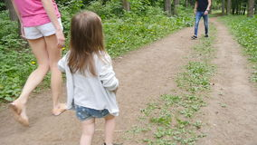 Χαριτωμένο κοριτσάκι που περπατά στο πάρκο με τους γονείς φιλμ μικρού μήκους