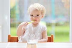 Χαριτωμένο κοριτσάκι που τρώει το γιαούρτι από το κουτάλι Στοκ Εικόνες