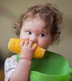 Χαριτωμένο κοριτσάκι που τρώει το καλαμπόκι στοκ φωτογραφίες