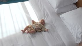 Χαριτωμένο κοριτσάκι στα άσπρα κλινοσκεπάσματα φιλμ μικρού μήκους