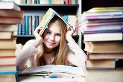 Χαριτωμένο κρύψιμο μικρών κοριτσιών στο πλαίσιο του βιβλίου κοντά στο σωρό των βιβλίων Στοκ Εικόνα