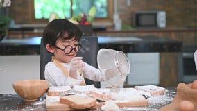 Χαριτωμένο λίγο ασιατικό αγόρι που κοσκινίζει το αλεύρι ζύμης με sifter το τρυπητό κόσκινων στην εγχώρια κουζίνα για προετοιμάζετ απόθεμα βίντεο
