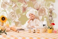 Χαριτωμένο λίγο μωρό προετοιμάζει τα νόστιμα γεύματα στην κουζίνα στοκ εικόνες
